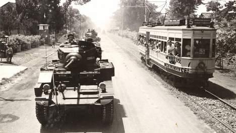 Hierbij de bijschrift: Britse tanks patrouilleren in de straten van Batavia. Op de tram onafhankelijkheidsleuzen. (Opname: 29-10-1945) BeeldbankWO2/NIOD Het originele pers-bijschrift luidt: 'Tanks of C Squadron, P.A.V.O. (11th Frontier Force) parade through Batavia, 29th October, 1945. The tank 'Cushlan' with C.O. Squadron, Major B.P. Boyd, in Oude Tamarinde Laan'.